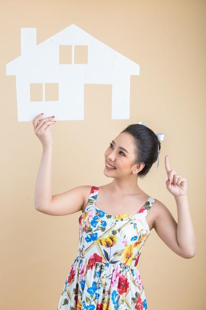 Retrato de joven feliz emocionada mujer asiática con papel a casa Foto gratis