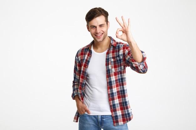 Retrato de un joven feliz mostrando gesto bien Foto gratis