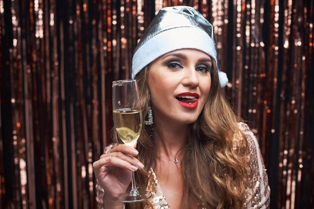 Retrato de joven feliz en plata santa sombrero con copa de champán en las manos. Foto Premium