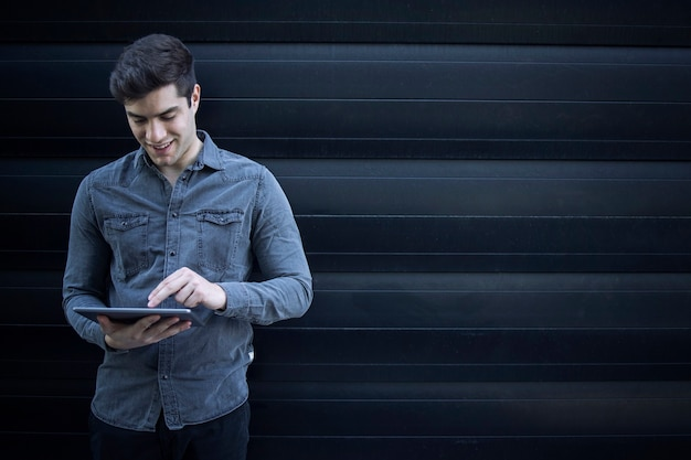 Retrato de joven guapo escribiendo en la computadora de la tableta y navegar por internet Foto gratis