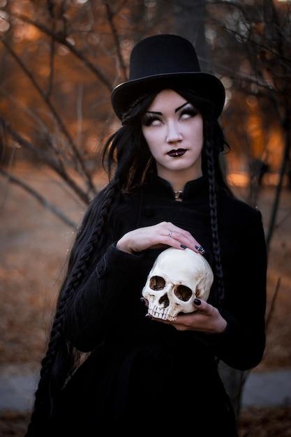 Retrato de joven hermosa con maquillaje oscuro en la cara y el esqueleto en las manos Foto Premium