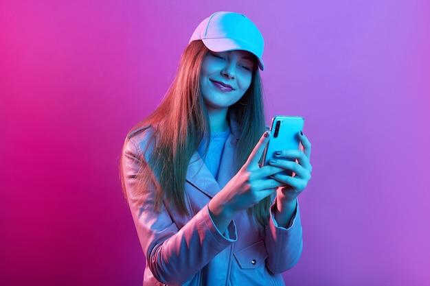 Retrato de joven hermosa modelo de moda con panadero de cuero y gorra de béisbol, sosteniendo el teléfono inteligente en las manos Foto gratis