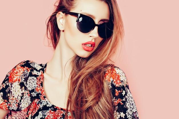 Retrato de joven hermosa mujer delgada en vestido sexy con labios sensuales con gafas de sol sonriendo y posando Foto Premium