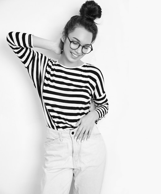 Retrato de joven hermosa mujer morena modelo chica con maquillaje desnudo en gafas en ropa hipster de verano posando junto a la pared. Foto gratis