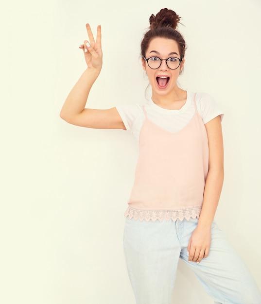 Retrato de joven hermosa mujer morena modelo chica con maquillaje desnudo en ropa de verano colorido hipster rosa posando junto a la pared. mostrando el signo de paz Foto gratis