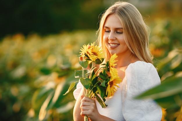 Retrato de joven hermosa mujer rubia en campo de girasoles en luz trasera. concepto de campo de verano mujer y girasoles. luz de verano. belleza al aire libre. Foto gratis