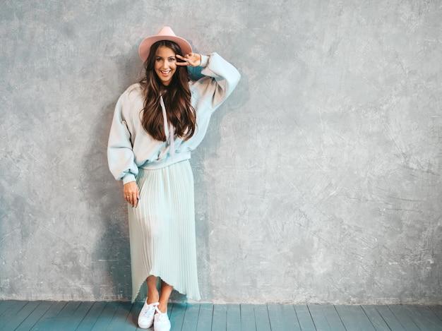 Retrato de joven hermosa mujer sonriente mirando. chica de moda en ropa casual de verano con capucha y falda. Foto gratis