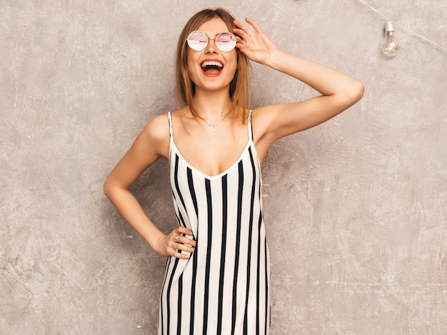 Retrato de joven hermosa niña sonriente en vestido de cebra de moda verano. mujer sexy despreocupada posando. modelo positivo divirtiéndose en gafas de sol redondas Foto gratis