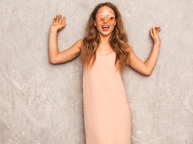 Retrato de joven hermosa niña sonriente en vestido rosa claro de moda verano. mujer sexy despreocupada posando. modelo positivo divirtiéndose en gafas de sol redondas Foto gratis