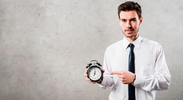Retrato de un joven hombre de negocios que señala en el reloj de alarma negro que se opone al muro de cemento gris Foto gratis