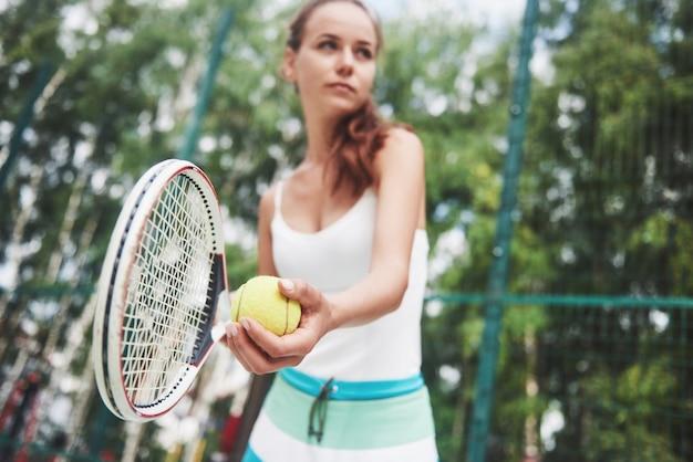Retrato de un joven jugador de tenis de pie listo para servir. Foto gratis