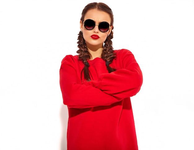 Retrato de joven modelo de mujer sonriente feliz con maquillaje brillante y labios coloridos con dos coletas y gafas de sol en ropa de verano rojo aislado. brazos cruzados Foto gratis