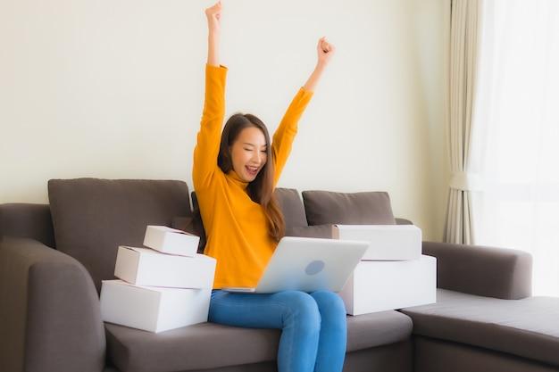 Retrato joven mujer asiática que usa la computadora portátil para trabajar con la caja de paquetería Foto gratis