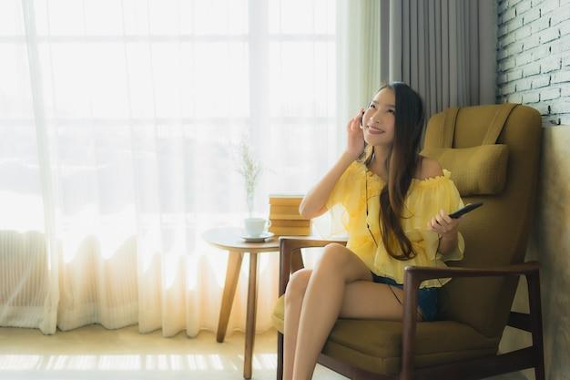 Retrato joven mujer asiática sentarse en la silla escuchar música con teléfono móvil café y libro Foto gratis