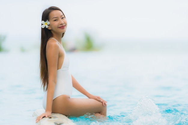 Retrato joven mujer asiática sonrisa feliz relajarse alrededor de la piscina en el hotel resort Foto gratis