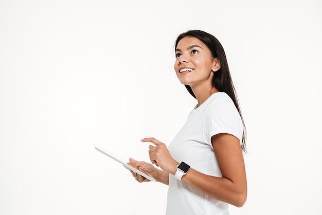 Retrato de una joven mujer feliz con tablet pc Foto gratis