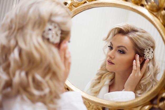 Retrato de joven mujer sexy en un vestido blanco mirando al espejo. Foto Premium