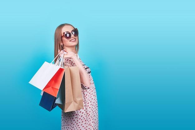 Retrato de joven mujer sonriente feliz con bolsas de compras en azul Foto Premium
