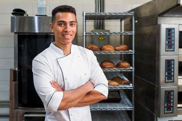 Retrato de un joven panadero de pie con los brazos cruzados en su panadería Foto gratis