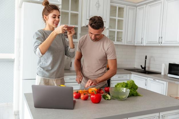 Retrato de una joven pareja amorosa cocinar ensalada juntos Foto gratis