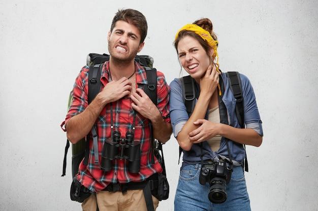 Retrato de una joven pareja enojada rascándose, sintiéndose molesto mientras es mordido por insectos exóticos o mosquitos, mirando a la cámara con expresión dolorosa en sus rostros. turismo, viajes y aventuras. Foto gratis