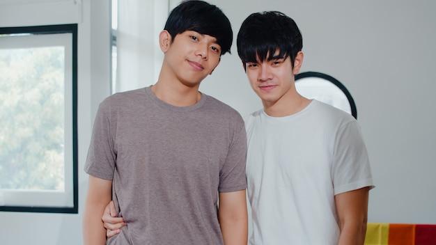 Retrato joven pareja gay asiática se siente feliz sonriendo en casa. los hombres asiáticos lgbtq relajan una sonrisa dentuda mirando a la cámara mientras se abrazan en la sala de estar en casa por la mañana. Foto gratis