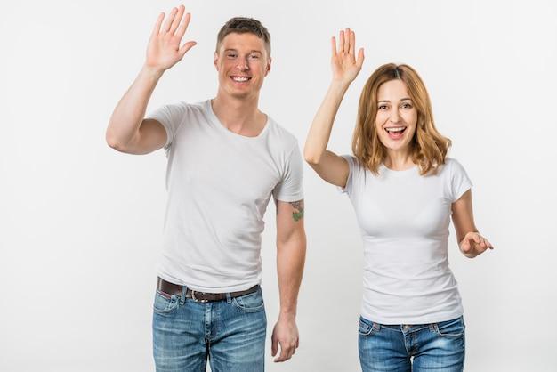Retrato de una joven pareja sonriente agitando sus manos mirando a la cámara Foto gratis