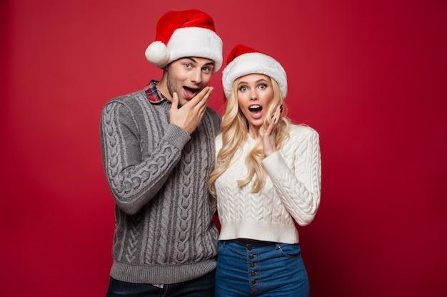Retrato de una joven pareja sorprendida en sombreros de navidad Foto gratis