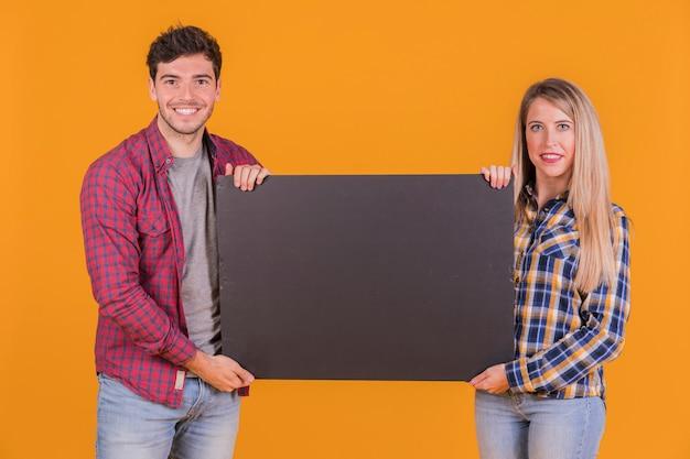 Retrato de una joven pareja sosteniendo un cartel negro en blanco sobre un fondo naranja Foto gratis
