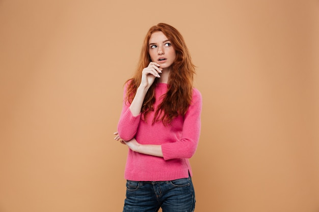 Retrato de una joven pelirroja pensativa mirando a otro lado Foto gratis