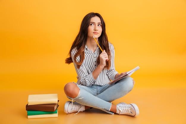 Retrato de una joven pensativa haciendo notas Foto gratis