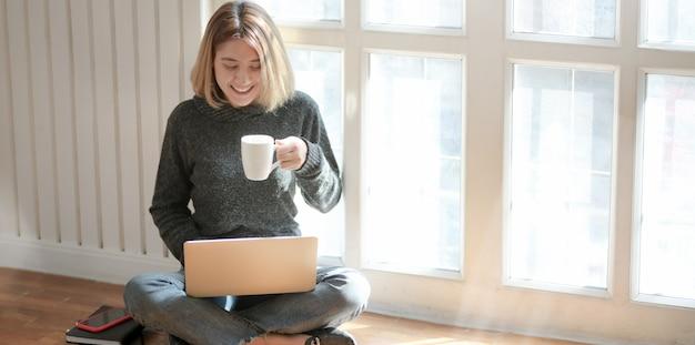 Retrato de joven profesional independiente que trabaja en su proyecto y bebe chocolate caliente mientras está sentada cerca de las ventanas Foto Premium