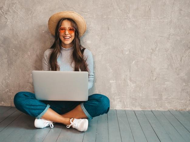 Retrato de joven sonriente creativa en gafas de sol. hermosa niña sentada en el piso cerca de la pared gris ... escribir y buscar información Foto gratis