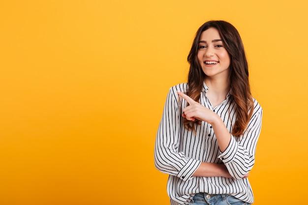 Retrato de una joven sonriente señalando con el dedo Foto gratis