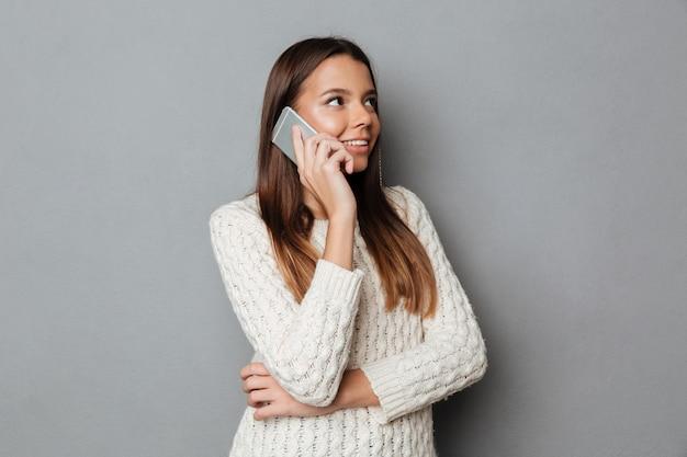 Retrato de una joven sonriente en suéter hablando Foto gratis