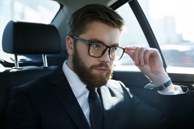 Retrato de un joven srious vistiendo traje y anteojos Foto gratis