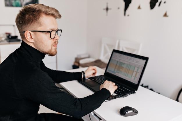 Retrato de joven trabajador en oficina en casa moderna blanca de cerca. retrato interior de hombre guapo de oficina Foto gratis