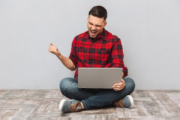 Retrato de un joven usando laptop y celebrando el éxito Foto gratis
