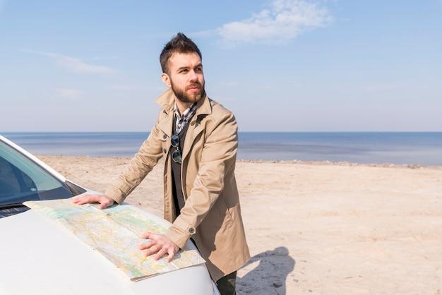 Retrato de un joven viajero masculino de pie en la playa con el mapa Foto gratis