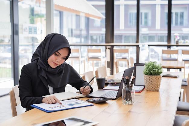 Retrato de jóvenes empresarios musulmanes con hiyab negro, trabajando en coworking. Foto Premium