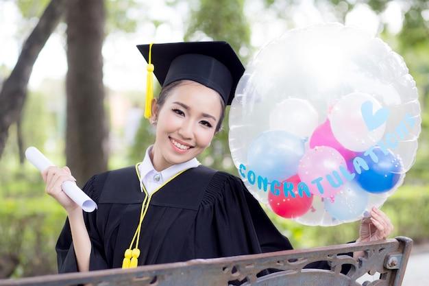 c35d7a382 Retrato de jóvenes graduados de mujeres felices vestido de graduación de  congrats en globo
