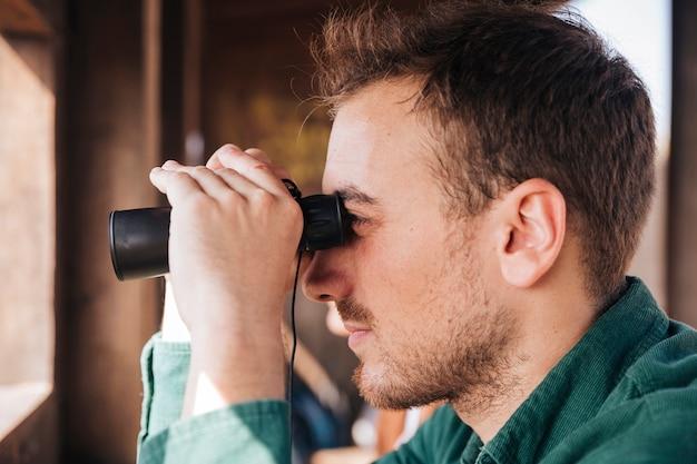 Retrato de lado de un hombre mirando a través de binoculares Foto gratis