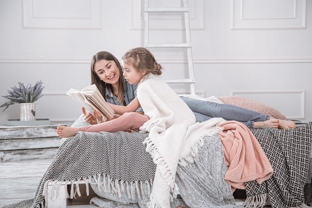 El retrato de una madre y de una hija lindas jovenes sonrientes que leen un libro que miente y se relaja en la cama en un cuarto blanco grande brillante. Foto gratis
