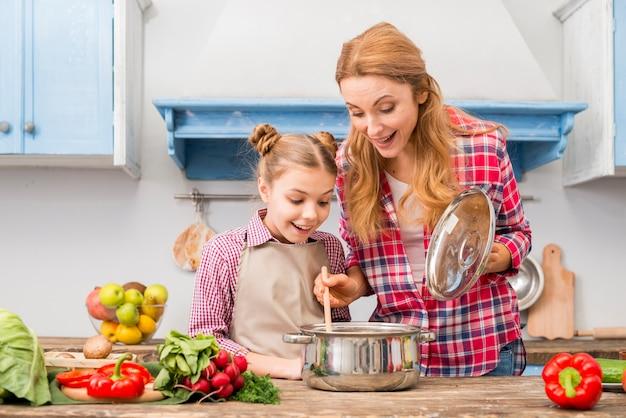 Retrato de una madre y una hija sonrientes mirando comida preparada en mesa de madera Foto gratis