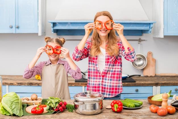 Retrato de una madre y una hija sonrientes que sostienen la rebanada de la pimienta roja delante de los ojos que miran la cámara Foto gratis
