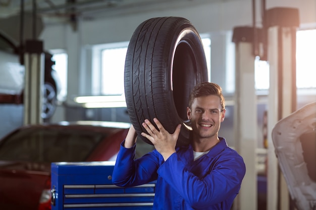 Retrato del mecánico que lleva un neumático Foto gratis
