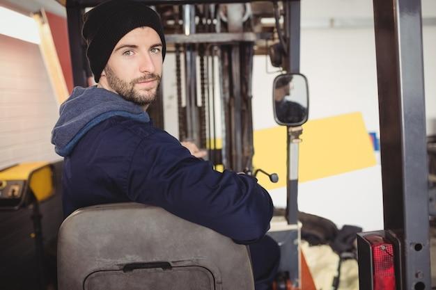 Retrato de mecánico sentado en carretilla elevadora Foto gratis