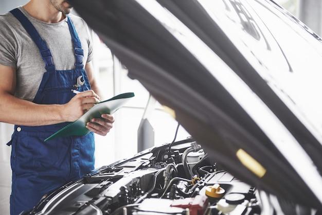 Retrato de un mecánico en el trabajo en su garaje Foto gratis