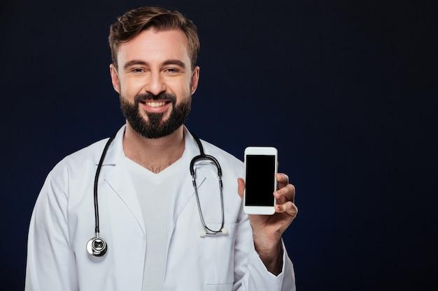 Retrato de un médico masculino feliz vestida con uniforme Foto gratis