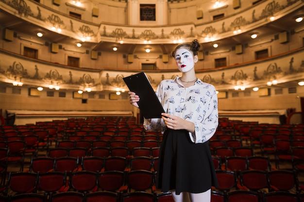 Retrato de mimo femenino de pie en un auditorio con guión Foto gratis